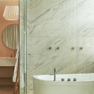 Immagine di una grande stanza da bagno padronale moderna con vasca freestanding, vasca/doccia, piastrelle rosa, piastrelle in ceramica, pareti rosa, pavimento in legno massello medio, lavabo da incasso, pavimento marrone, porta doccia a battente e top grigio