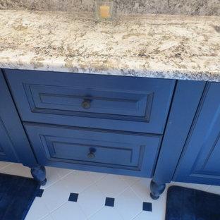 Diseño de cuarto de baño tradicional, de tamaño medio, con armarios con paneles con relieve, puertas de armario azules, paredes amarillas, suelo de baldosas de porcelana, lavabo bajoencimera y encimera de granito