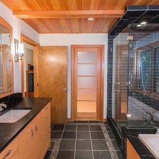 Ispirazione per una stanza da bagno design con lavabo sottopiano, ante lisce, ante in legno scuro, top in granito, vasca da incasso, doccia alcova, WC monopezzo, piastrelle nere e piastrelle a listelli