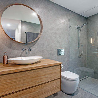 Design ideas for a mid-sized contemporary 3/4 bathroom in Sunshine Coast with medium wood cabinets, gray tile, porcelain tile, grey walls, porcelain floors, a vessel sink, wood benchtops, grey floor, an open shower, flat-panel cabinets, a curbless shower, a one-piece toilet and brown benchtops.