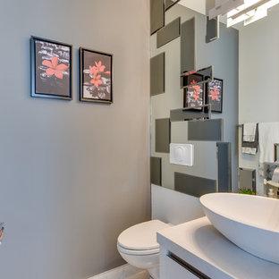 Diseño de cuarto de baño con ducha, contemporáneo, de tamaño medio, con armarios con paneles lisos, puertas de armario blancas, bañera empotrada, combinación de ducha y bañera, sanitario de una pieza, baldosas y/o azulejos grises, baldosas y/o azulejos con efecto espejo, paredes grises, suelo de madera en tonos medios, lavabo sobreencimera y encimera de cuarzo compacto