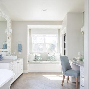 Ispirazione per una grande stanza da bagno padronale stile marino con vasca freestanding, pareti grigie, parquet chiaro, top in quarzo composito, consolle stile comò, ante bianche, lavabo a bacinella, pavimento beige e top grigio