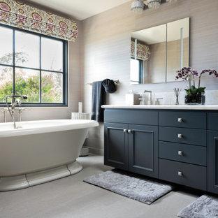 Ejemplo de cuarto de baño papel pintado, tradicional renovado, papel pintado, con armarios con paneles empotrados, puertas de armario negras, bañera exenta, paredes grises, lavabo bajoencimera, suelo gris, encimeras blancas y papel pintado