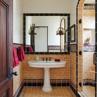 Foto di una stanza da bagno mediterranea con lavabo a colonna, pareti bianche e piastrelle arancioni
