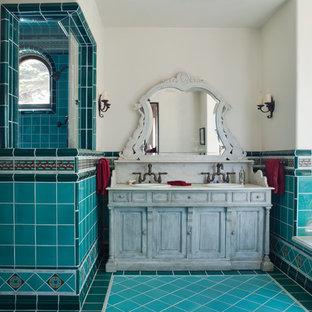 Réalisation d'une salle de bain méditerranéenne avec un lavabo posé, un placard en trompe-l'oeil, des portes de placard grises, un carrelage bleu, un mur blanc et un sol turquoise.