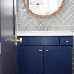 Imagen de cuarto de baño con ducha, contemporáneo, de tamaño medio, con armarios estilo shaker, puertas de armario azules, bañera encastrada, combinación de ducha y bañera, sanitario de una pieza, baldosas y/o azulejos blancos, baldosas y/o azulejos de vidrio, paredes blancas, lavabo encastrado, encimera de cuarcita y ducha con cortina
