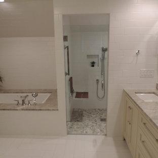 ローリーの中サイズのトランジショナルスタイルのおしゃれなマスターバスルーム (シェーカースタイル扉のキャビネット、ベージュのキャビネット、アンダーマウント型浴槽、段差なし、分離型トイレ、白いタイル、セラミックタイル、白い壁、セラミックタイルの床、アンダーカウンター洗面器、珪岩の洗面台、白い床、開き戸のシャワー) の写真