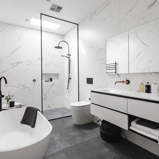 This is an example of a contemporary bathroom in Melbourne with flat-panel cabinets, white cabinets, a freestanding tub, a curbless shower, white tile, an integrated sink, grey floor, an open shower, white benchtops and a floating vanity.