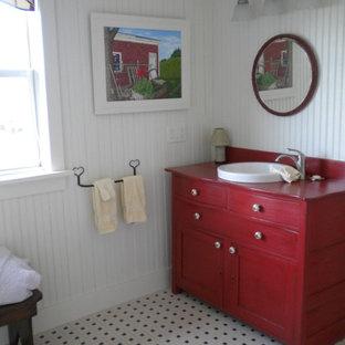Ejemplo de cuarto de baño con ducha, de estilo de casa de campo, de tamaño medio, con armarios con paneles empotrados, puertas de armario rojas, sanitario de una pieza, paredes blancas, suelo de baldosas de porcelana, lavabo encastrado, encimera de madera y encimeras rojas