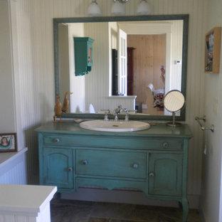 Mittelgroßes Landhausstil Duschbad mit Schrankfronten mit vertiefter Füllung, türkisfarbenen Schränken, Toilette mit Aufsatzspülkasten, weißer Wandfarbe, Schieferboden, Einbauwaschbecken, Waschtisch aus Holz und türkiser Waschtischplatte in Sonstige