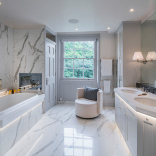 Design ideas for a medium sized classic bathroom in London with recessed-panel cabinets, white cabinets, a built-in bath, marble tiles, white walls, marble flooring and white floors.