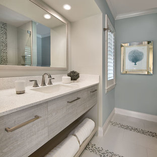 Example of a mid-sized beach style master ceramic floor bathroom design in Miami with flat-panel cabinets, light wood cabinets, blue walls, an undermount sink and laminate countertops