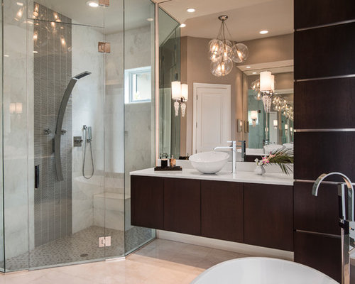 ... cabinets, dark wood cabinets, a freestanding tub, an alcove shower and