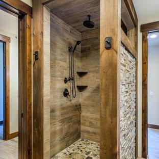 Diseño de cuarto de baño con ducha, rural, de tamaño medio, con armarios estilo shaker, puertas de armario de madera en tonos medios, ducha esquinera, sanitario de dos piezas, paredes beige, suelo de baldosas de porcelana, encimera de granito, baldosas y/o azulejos marrones, baldosas y/o azulejos multicolor y baldosas y/o azulejos de piedra