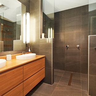 Imagen de cuarto de baño asiático, de tamaño medio, con puertas de armario de madera clara, ducha abierta, sanitario de una pieza, baldosas y/o azulejos verdes, baldosas y/o azulejos de porcelana, paredes verdes, suelo de baldosas de porcelana, lavabo sobreencimera, encimera de laminado, suelo gris y ducha abierta