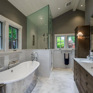 This is an example of a large classic ensuite bathroom in Tampa with freestanding cabinets, dark wood cabinets, a freestanding bath, a corner shower, white tiles, metro tiles, grey walls, marble flooring, a submerged sink, marble worktops, white floors and a hinged door.