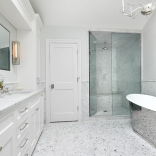Inspiration for a large classic ensuite bathroom in Tampa with a hinged door, beaded cabinets, white cabinets, a freestanding bath, an alcove shower, grey tiles, white tiles, marble tiles, grey walls, marble flooring, a submerged sink, marble worktops and white floors.