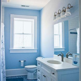 Foto de cuarto de baño con ducha, clásico, de tamaño medio, con armarios con paneles empotrados, puertas de armario blancas, bañera esquinera, combinación de ducha y bañera, sanitario de dos piezas, paredes azules, suelo de baldosas tipo guijarro, lavabo bajoencimera y encimera de acrílico