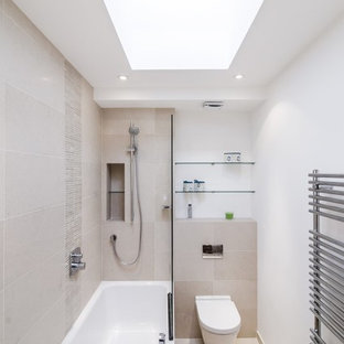 Inspiration for a mid-sized contemporary master bathroom in London with a shower/bathtub combo, a wall-mount toilet, beige tile, porcelain tile, white walls, porcelain floors and an alcove tub.