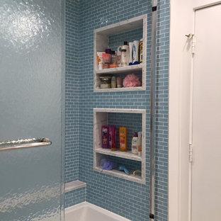 Immagine di una stanza da bagno contemporanea di medie dimensioni con ante con riquadro incassato, ante bianche, vasca ad alcova, vasca/doccia, piastrelle blu, piastrelle di vetro, pareti bianche e top in quarzite