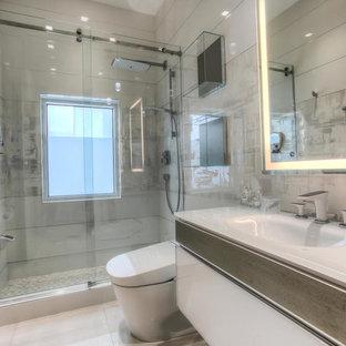 Стильный дизайн: ванная комната среднего размера в современном стиле с плоскими фасадами, белыми фасадами, душем в нише, биде, серой плиткой, керамогранитной плиткой, серыми стенами, полом из керамогранита, душевой кабиной, монолитной раковиной и стеклянной столешницей - последний тренд