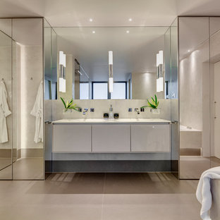 Design ideas for a large contemporary ensuite bathroom in Devon with a built-in bath, beige walls, porcelain flooring, beige floors, flat-panel cabinets and white cabinets.