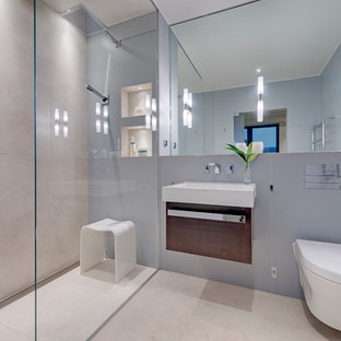 This is an example of a medium sized contemporary ensuite bathroom in Devon with freestanding cabinets, dark wood cabinets, a walk-in shower, a wall mounted toilet, beige tiles, porcelain tiles, beige walls, porcelain flooring, a wall-mounted sink, beige floors and an open shower.