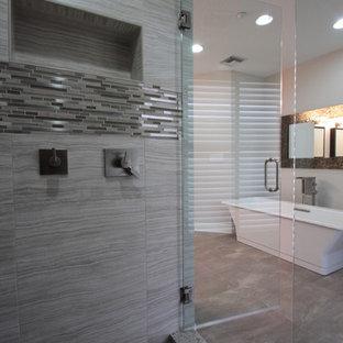 Imagen de cuarto de baño costero, grande, con armarios estilo shaker, puertas de armario de madera en tonos medios, bañera exenta, azulejos en listel, paredes beige, suelo vinílico, lavabo sobreencimera y encimera de granito