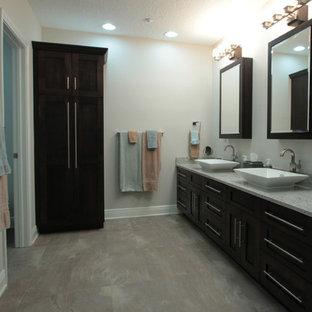 Foto de cuarto de baño marinero, grande, con armarios estilo shaker, puertas de armario de madera en tonos medios, bañera exenta, azulejos en listel, paredes beige, suelo vinílico, lavabo sobreencimera y encimera de granito