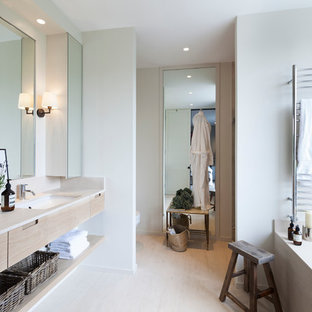 Design ideas for a scandinavian ensuite bathroom in London with a submerged sink, light wood cabinets, a submerged bath, light hardwood flooring, flat-panel cabinets and white walls.
