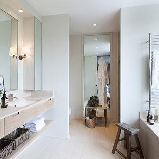 На фото: главная ванная комната в скандинавском стиле с врезной раковиной, светлыми деревянными фасадами, полновстраиваемой ванной, светлым паркетным полом, плоскими фасадами и белыми стенами с