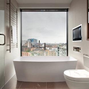 ロンドンの小さいコンテンポラリースタイルのおしゃれなマスターバスルーム (置き型浴槽、壁掛け式トイレ、ベージュの壁、ベージュのタイル、茶色い床) の写真