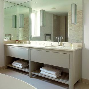 Immagine di una stanza da bagno chic con lavabo da incasso, ante lisce, ante grigie, top in pietra calcarea e vasca freestanding