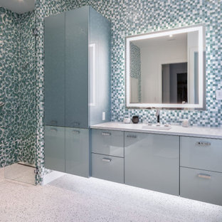 Inspiration for a large contemporary master multicolored tile terrazzo floor and multicolored floor walk-in shower remodel in Tampa with flat-panel cabinets, blue cabinets, a wall-mount toilet, quartz countertops, a hinged shower door, white countertops and an undermount sink