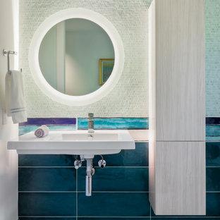 Cette photo montre une petite salle d'eau tendance avec un placard à porte plane, un carrelage bleu, sol en terrazzo, un lavabo suspendu, un mur blanc et un sol gris.