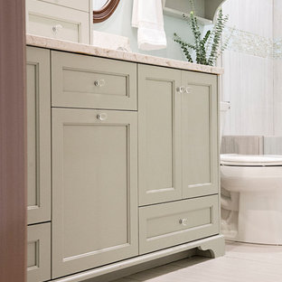 ナッシュビルの中サイズのシャビーシック調のおしゃれなバスルーム (浴槽なし) (落し込みパネル扉のキャビネット、緑のキャビネット、一体型トイレ、グレーのタイル、セラミックタイル、青い壁、セラミックタイルの床、アンダーカウンター洗面器、珪岩の洗面台、グレーの床、マルチカラーの洗面カウンター) の写真