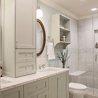 ナッシュビルの中サイズのシャビーシック調のおしゃれなバスルーム (浴槽なし) (落し込みパネル扉のキャビネット、緑のキャビネット、アルコーブ型シャワー、一体型トイレ、グレーのタイル、セラミックタイル、青い壁、セラミックタイルの床、アンダーカウンター洗面器、珪岩の洗面台、グレーの床、開き戸のシャワー、マルチカラーの洗面カウンター) の写真