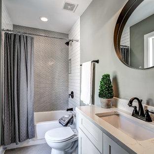 Пример оригинального дизайна: маленькая ванная комната в стиле современная классика с белыми фасадами, разноцветной плиткой, керамической плиткой, столешницей из искусственного кварца, ванной в нише, душем над ванной, раздельным унитазом, серыми стенами, полом из керамогранита, врезной раковиной, серым полом и шторкой для душа