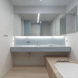 Esempio di una stanza da bagno contemporanea con pareti bianche, parquet chiaro e ante di vetro
