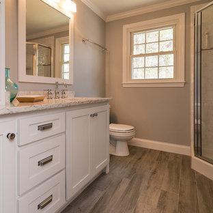Imagen de cuarto de baño minimalista, de tamaño medio, con armarios estilo shaker, puertas de armario blancas, ducha esquinera, paredes grises, suelo de madera oscura, lavabo suspendido y encimera de mármol