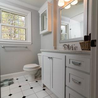 Esempio di una stanza da bagno moderna di medie dimensioni con ante in stile shaker, ante bianche, doccia ad angolo, pareti grigie, pavimento in vinile, lavabo sospeso e top in marmo