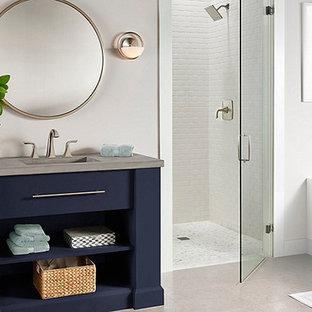 Idee per una stanza da bagno padronale tradizionale di medie dimensioni con consolle stile comò, ante blu, vasca ad alcova, doccia alcova, pareti grigie, pavimento in laminato, lavabo integrato, top in cemento, pavimento grigio e porta doccia a battente