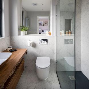 Imagen de cuarto de baño con ducha, contemporáneo, pequeño, con ducha esquinera, sanitario de una pieza, baldosas y/o azulejos grises, baldosas y/o azulejos de mármol, paredes grises, suelo de linóleo, lavabo de seno grande, encimera de madera, suelo blanco, ducha abierta, armarios con paneles lisos, puertas de armario de madera oscura y encimeras marrones