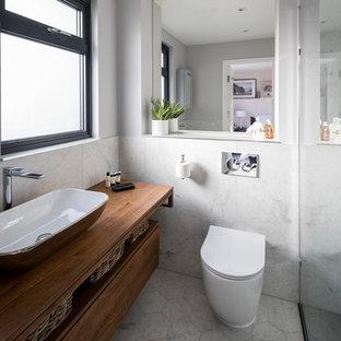 Immagine di una stanza da bagno padronale moderna con consolle stile comò, ante marroni, doccia ad angolo, WC monopezzo, piastrelle grigie, piastrelle di marmo, pareti grigie, pavimento in linoleum, lavabo rettangolare, top in legno, pavimento bianco e doccia aperta