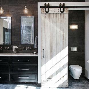 На фото: большая главная ванная комната в стиле фьюжн с врезной раковиной, фасадами с утопленной филенкой, черными фасадами, мраморной столешницей, отдельно стоящей ванной, душем без бортиков, инсталляцией, серой плиткой, каменной плиткой, белыми стенами и мраморным полом с