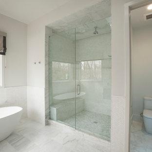Idéer för att renovera ett mellanstort funkis en-suite badrum, med släta luckor, blå skåp, ett fristående badkar, en dusch i en alkov, en toalettstol med hel cisternkåpa, vit kakel, porslinskakel, vita väggar, klinkergolv i porslin, ett integrerad handfat, bänkskiva i akrylsten, vitt golv och dusch med gångjärnsdörr