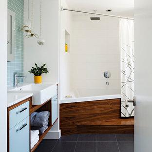 Ispirazione per una stanza da bagno contemporanea con lavabo da incasso, ante lisce, ante blu, piastrelle blu, pavimento nero e top bianco