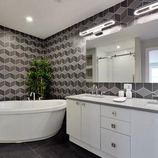 Modernes Badezimmer En Suite mit flächenbündigen Schrankfronten, weißen Schränken, freistehender Badewanne, Unterbauwaschbecken, schwarzer Wandfarbe und schwarzem Boden in Ottawa