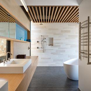 Modern inredning av ett brun brunt badrum, med släta luckor, skåp i mellenmörkt trä, ett fristående badkar, beige kakel, beige väggar, betonggolv, ett fristående handfat, träbänkskiva och grått golv
