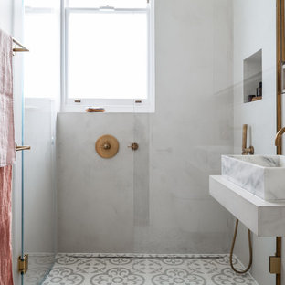 Photo of a contemporary bathroom in London with an alcove shower, grey walls, a vessel sink, grey floors, a hinged door and white worktops.